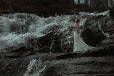 Katerina Klio WOMAN IN WHITE LACE STANDING BY WATERFALL