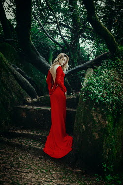 Katerina Klio WOMAN IN RED BY STEPS OF MOSSY GARDEN