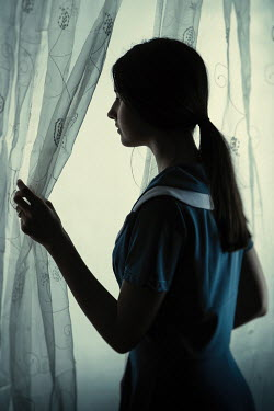 Magdalena Russocka young girl looking through curtains inside