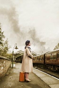 Stephen Mulcahey 1940S WOMAN WITH SUITCASE ON RAILWAY PLATFORM