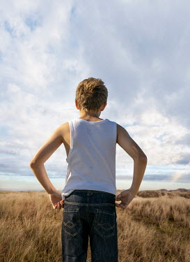 Stephen Mulcahey YOUNG BOY IN JEANS STANDING IN COUNTRYSIDE