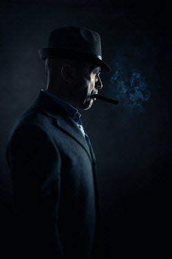 Paolo Martinez MAN WITH HAT AND CIGAR STANDING IN SHADOW