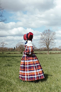 Matilda Delves HISTORICAL WOMAN WITH BONNET STANDING IN FIELD