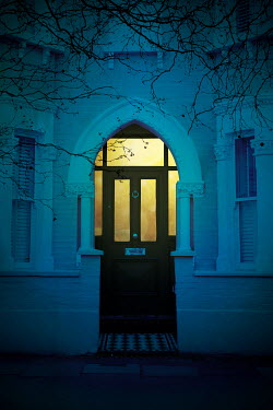 Miguel Sobreira LIGHT SHINING IN DOOR OF HOUSE AT DUSK