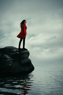 Magdalena Russocka modern woman standing on rock by sea