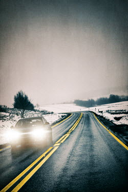 Magdalena Russocka car with headlights driving on country road in winter