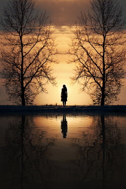 Magdalena Russocka silhouette of trees and woman  standing by water at sunset