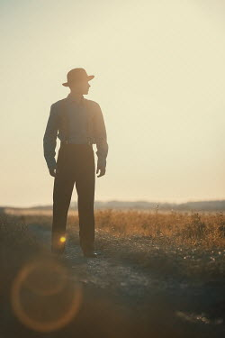 Magdalena Russocka vintage man standing on country road at sunset