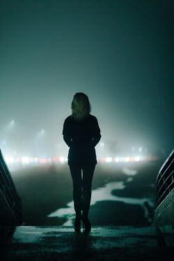 Evelina Kremsdorf WOMAN ON STEPS WATCHING CAR LIGHTS AT NIGHT