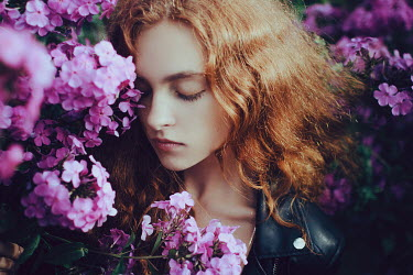 Irina Orwald GIRL WITH RED HAIR BY PINK FLOWERS OUTDOORS