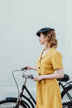 Matilda Delves RETRO WOMAN WITH HAT PUSHING BICYCLE