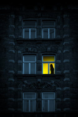 Magdalena Russocka silhouette of woman in illuminated window of old building at night