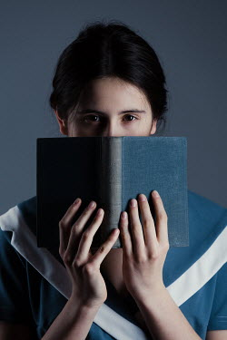 Magdalena Russocka teenage girl hiding behind book inside