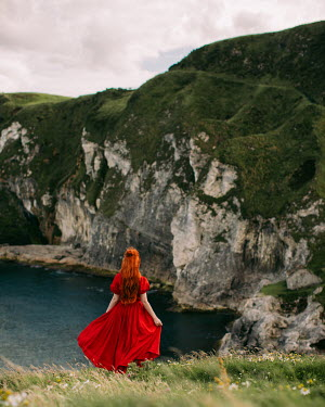 Rebecca Stice WOMAN WITH RED HAIR AND DRESS ON CLIFF BY SEA