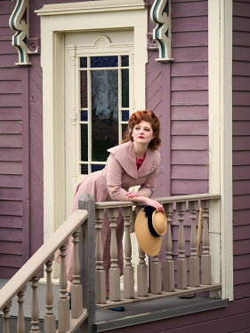 Elisabeth Ansley WOMAN WITH RED HAIR LEANING ON BALCONY OF HOUSE