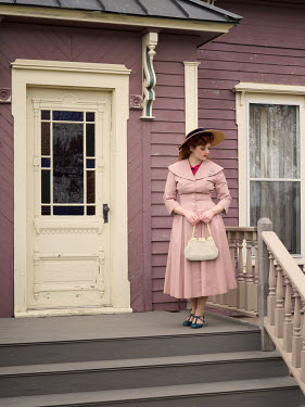 Elisabeth Ansley RETRO WOMAN IN HAT STANDING OUTSIDE HOUSE