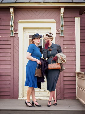 Elisabeth Ansley RETRO WOMAN WHISPERING TO FRIEND OUTSIDE HOUSE