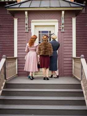 Elisabeth Ansley GROUP OF RETRO WOMEN OUTSIDE HOUSE