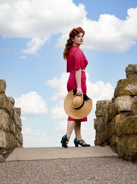 Elisabeth Ansley RETRO WOMAN WITH RED HAIR HOLDING HAT OUTDOORS