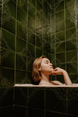 Esme Mai WOMAN RELAXING IN BATH WITH GREEN TILES