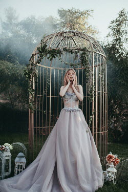 Jovana Rikalo WOMAN IN GARDEN STANDING BY LARGE BIRDCAGE