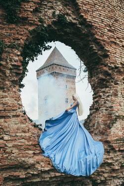 Jovana Rikalo BLONDE WOMAN IN HOLE IN WALL BY CASTLE