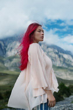 Tatiana Mertsalova WOMAN WITH PINK HAIR BY CLIFFS WITH CLOUDS