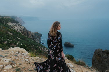 Tatiana Mertsalova WOMAN IN FLORAL DRESS ON CLIFF BY SEA
