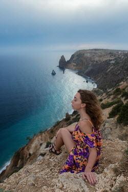Tatiana Mertsalova WOMAN IN FLORAL DRESS SITTING ON CLIFF BY SEA