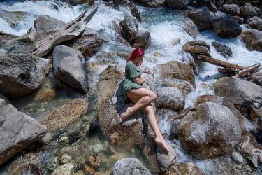 Tatiana Mertsalova WOMAN WITH PINK HAIR LYING ON ROCKS BY RIVER