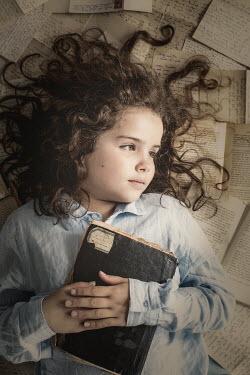 Des Panteva LITTLE GIRL LYING ON LETTERS HOLDING BOOK
