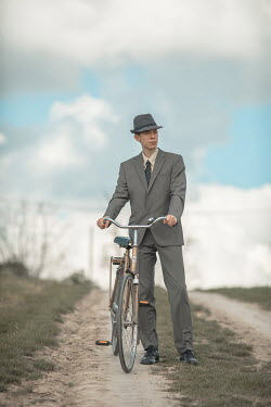 Ildiko Neer Retro man in suit standing with bicycle