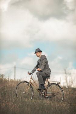 Ildiko Neer Retro man in suit sitting on bicycle