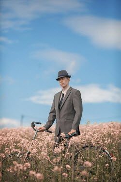 Ildiko Neer Retro man in suit standing with bicycle in meadow