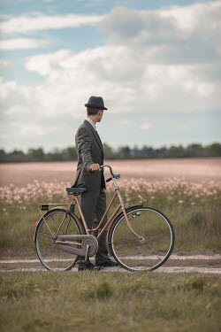 Ildiko Neer Retro man in suit standing with bicycle