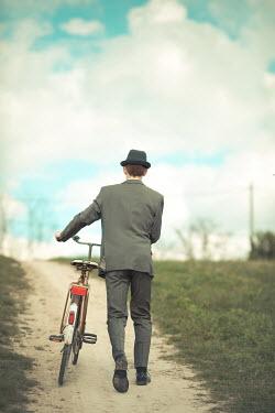 Ildiko Neer Retro man in suit pushing bicycle