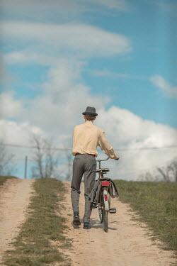Ildiko Neer Retro man pushing bicycle
