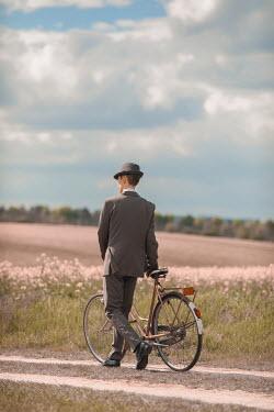 Ildiko Neer Retro man in suit walking with bicycle