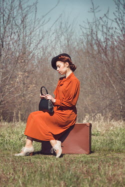 Joanna Czogala RETRO WOMAN SITTING ON SUITCASE IN COUNTRYSIDE