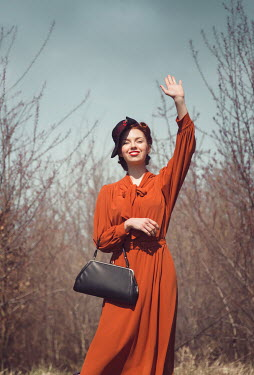 Joanna Czogala RETRO WOMAN IN HAT WAVIING IN COUNTRYSIDE