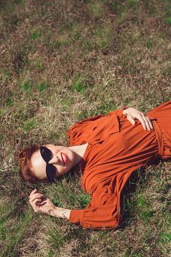 Joanna Czogala RETRO WOMAN IN SUNGLASSES LYING ON GRASS