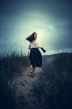 Marie Carr BRUNETTE WOMAN RUNNING IN SAND DUNES