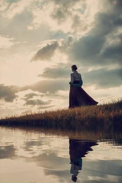 Magdalena Russocka historical woman walking by river at sunset