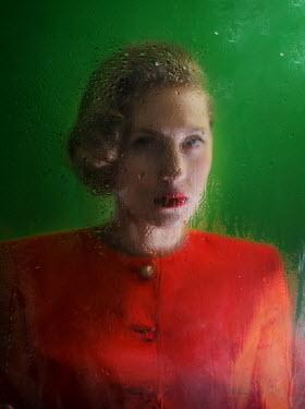 Svitozar Bilorusov BLONDE WOMAN IN RED BEHIND WET GLASS