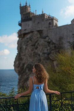 Tatiana Mertsalova WOMAN IN SUMMER DRESS BELOW CASTLE BY SEA