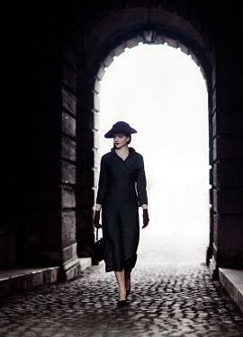 Nikaa RETRO WOMAN WITH HAT WALKING IN TUNNEL