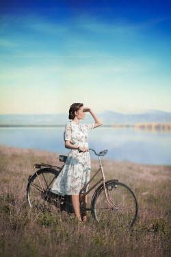 Ildiko Neer woman standing by lake with bicycle