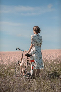 Ildiko Neer Timeless woman standing with bicycle in meadow