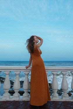 Tatiana Mertsalova WOMAN ON BALCONY BY SEA AT DUSK
