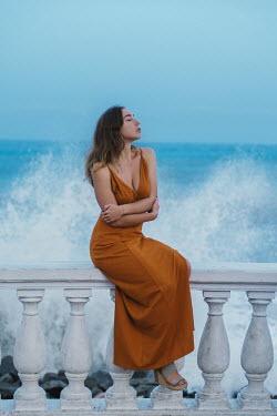 Tatiana Mertsalova WOMAN SITTING ON WALL WITH CRASHING WAVE